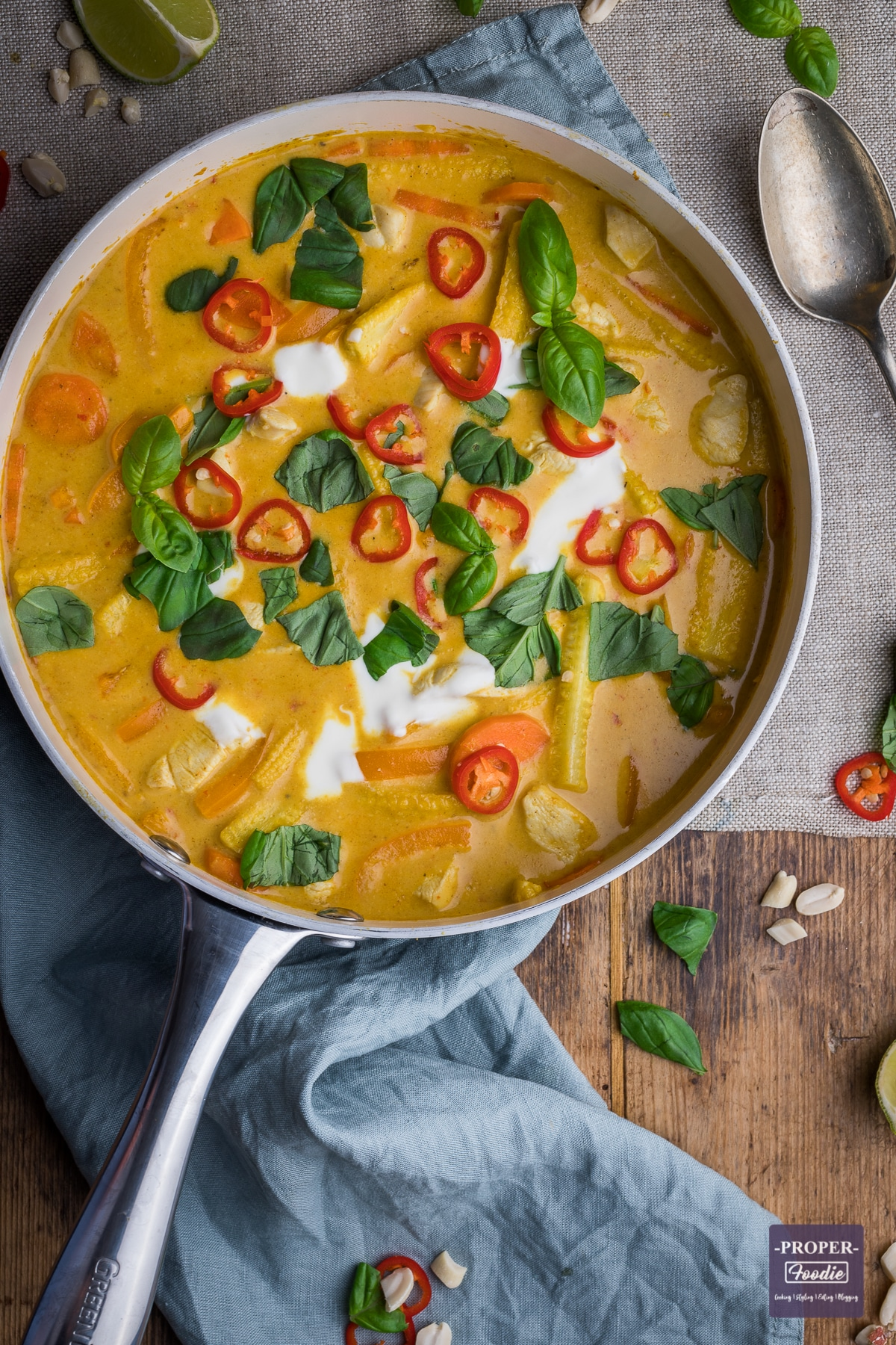 Chicken panang curry in a large pan and topped with yogurt, fresh red chillies and fresh basil leaves