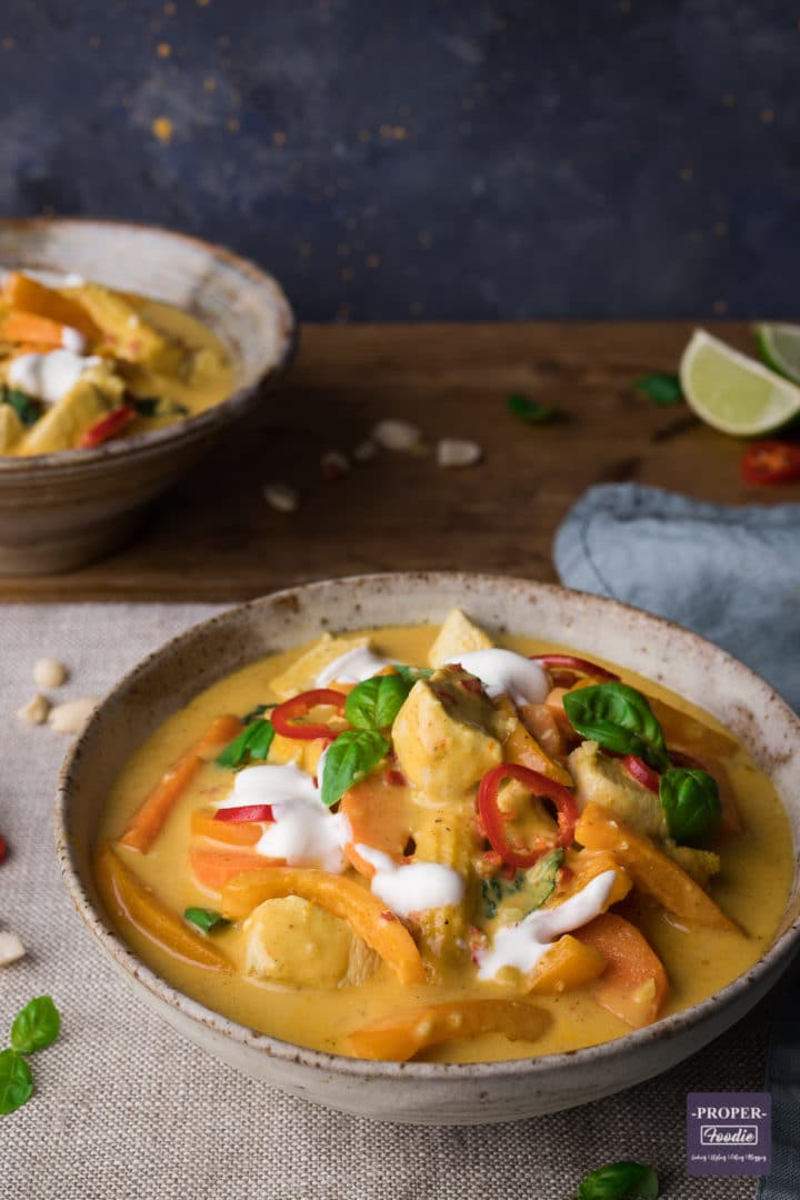 chicken Panang curry with a yellow sauce served in a bowl and topped with yogurt and chilli