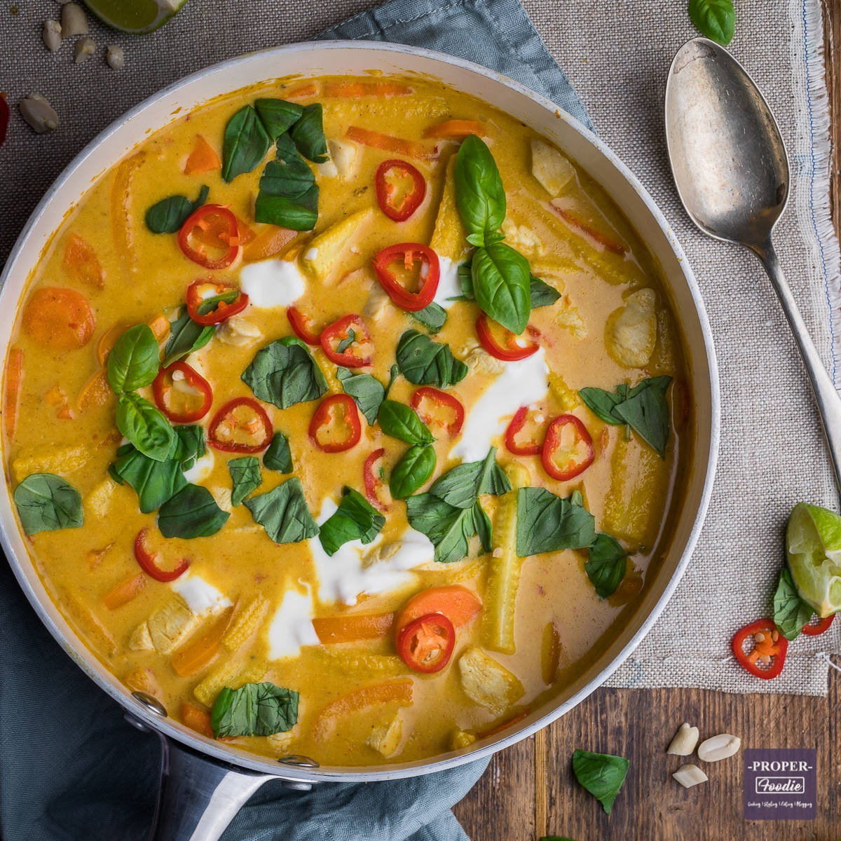 Thai Panang curry in a large pan with yogurt and fresh chillies