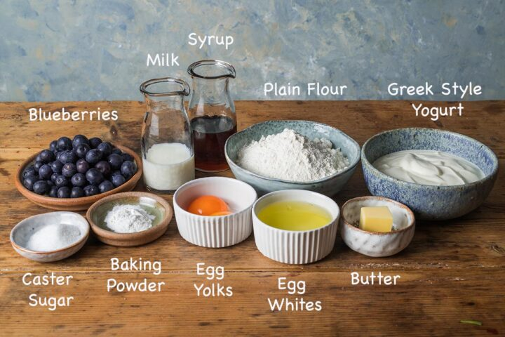 A display of the ingredients needed to make Blueberry American style pancakes with text overlay stating each ingredients