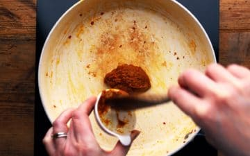 adding Thai yellow paste to a pan on the heat