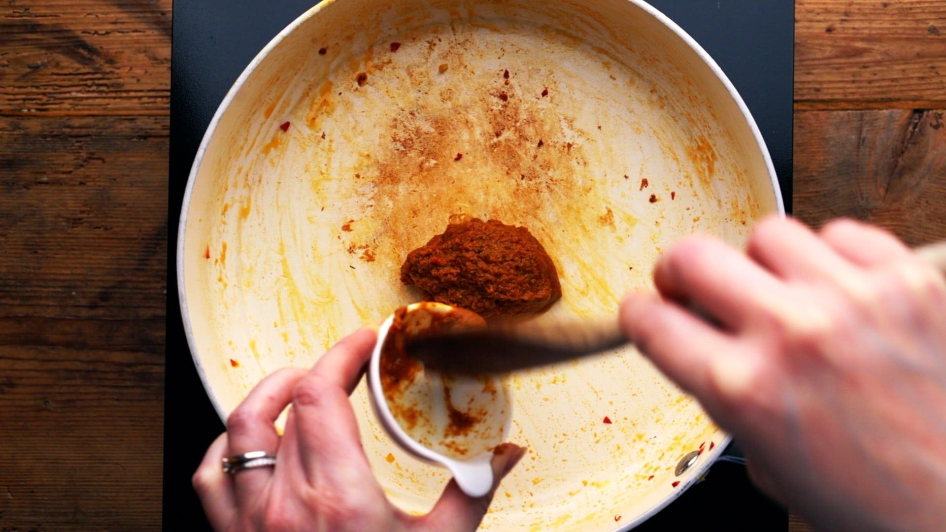 adding Thai yellow paste to a hot pan
