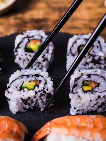 california rolls served on a black slate platter with a pair of chopsticks