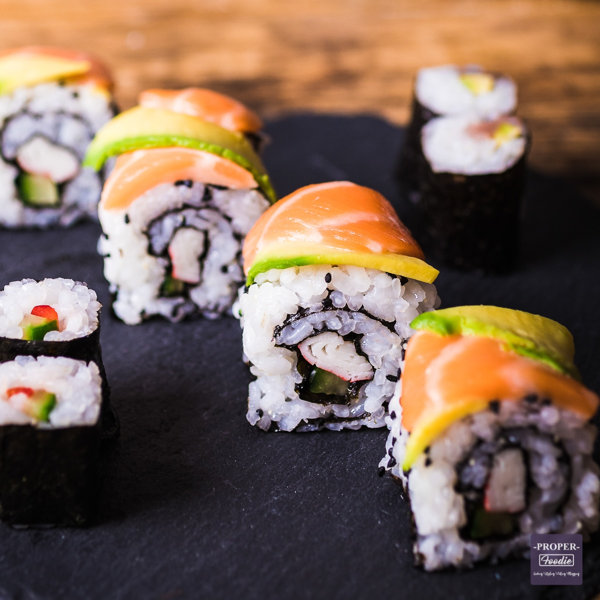 four pieces of sushi with slices of salmon and avocado on the top to mimic a dragon