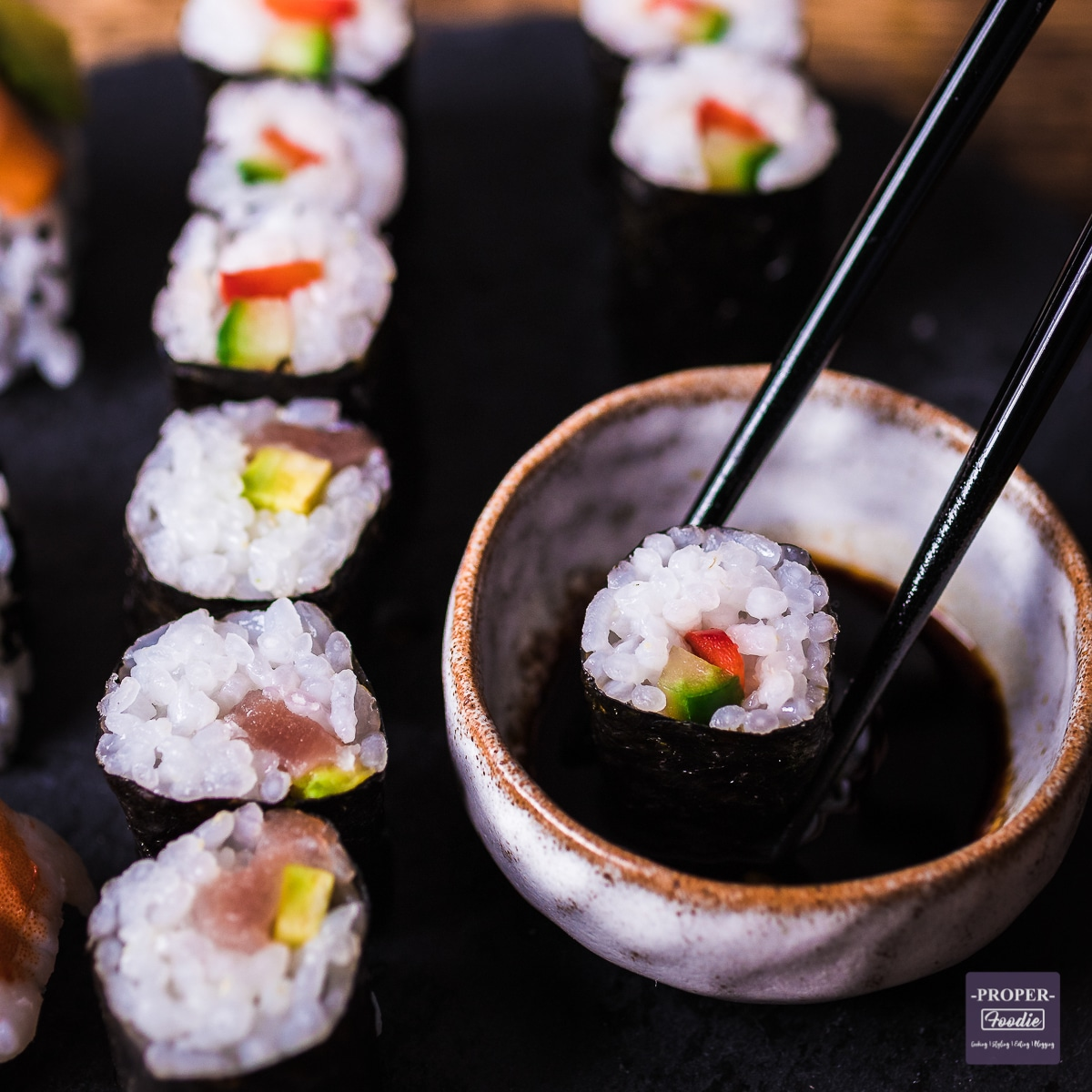 maki sushi on a platter with one piece being dipped in soy sauce with chop sticks