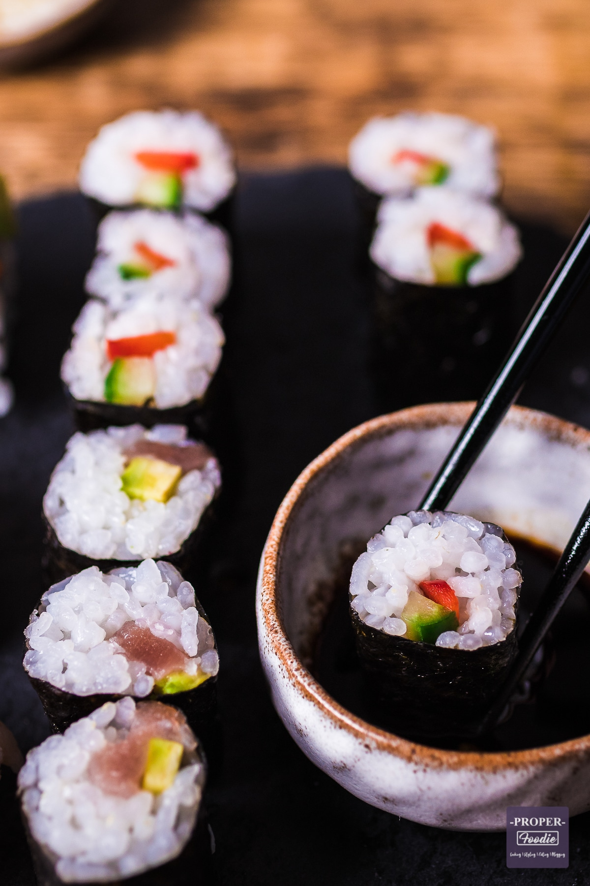 maki sushi on black slate with one piece being dipped in soy sauce