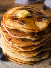 Stack of American style blueberry pancakes with a piece of butter on top and syrup being poured over