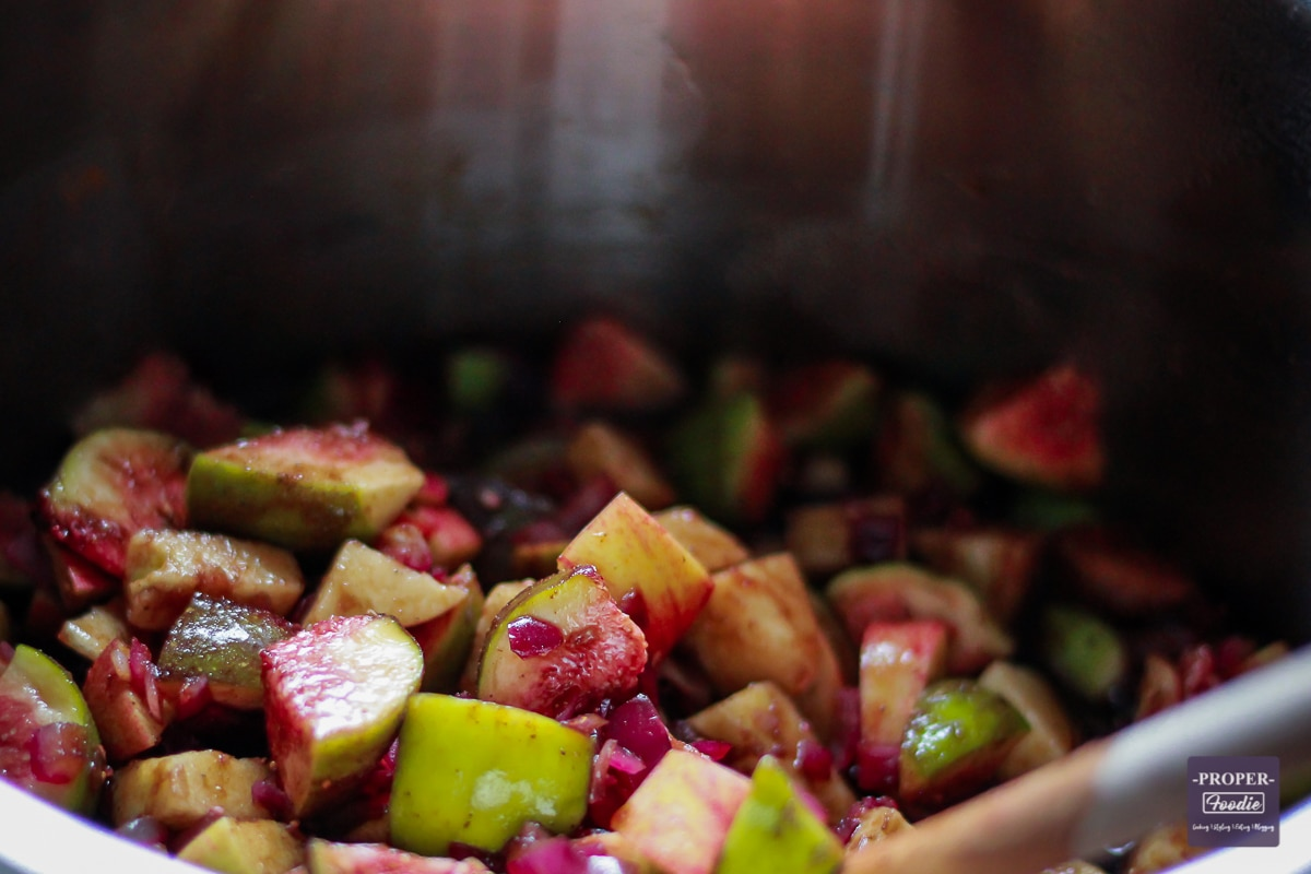 chopped figs and apples cooking in a large pan
