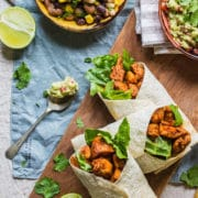 three healthy chicken wraps on a board with a spoonful of guacamole next to them and the edge of a bowl of mixed bean salad just visible