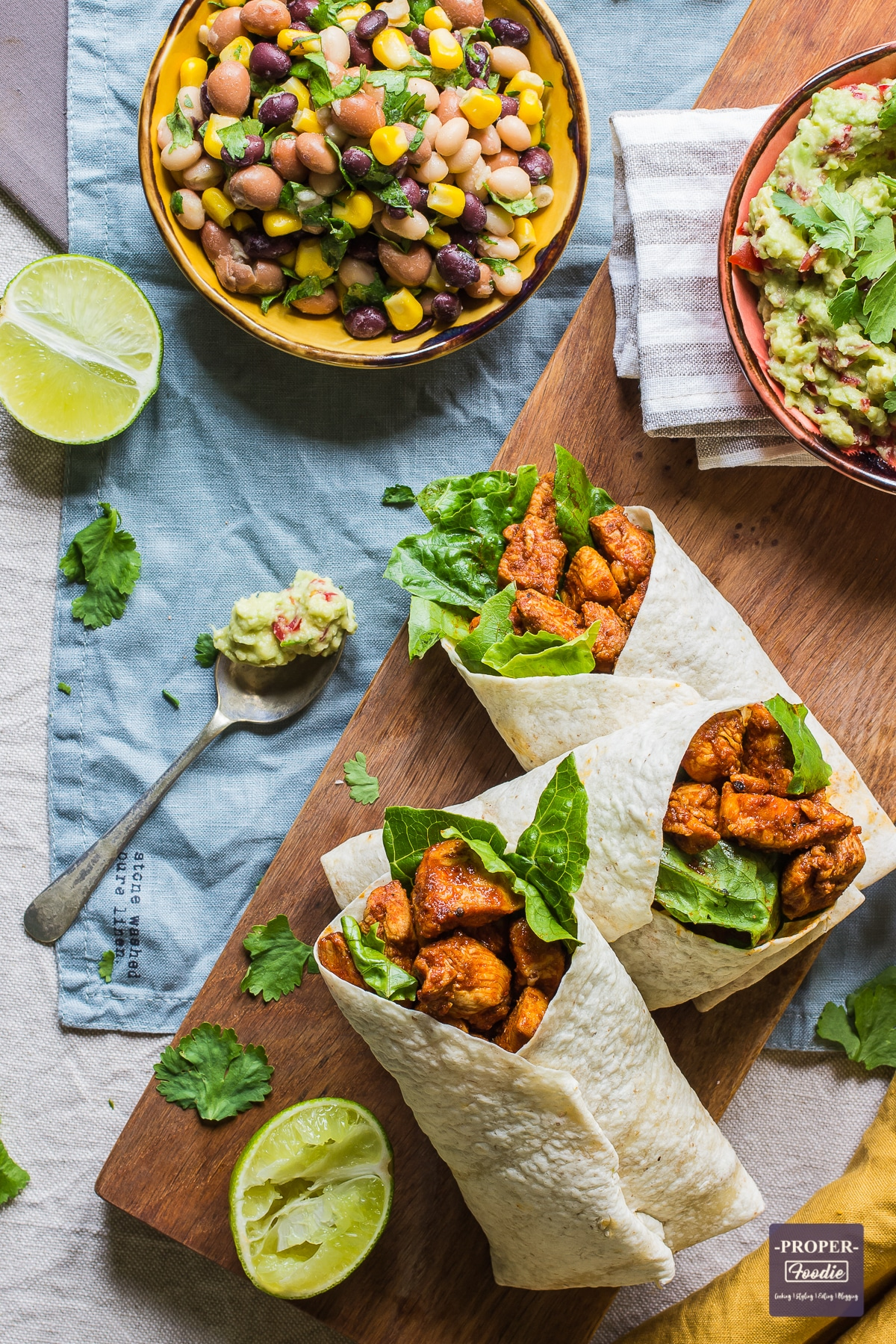 three wraps with paprika chicken and a spoonful of guacamole next to them and the edge of a bowl of mixed bean salad just visible