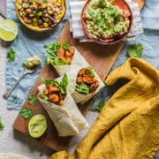 three chicken wraps on a board viewed from above with half a lime squeezed at the side and small bowls of bean salad and guacamole above