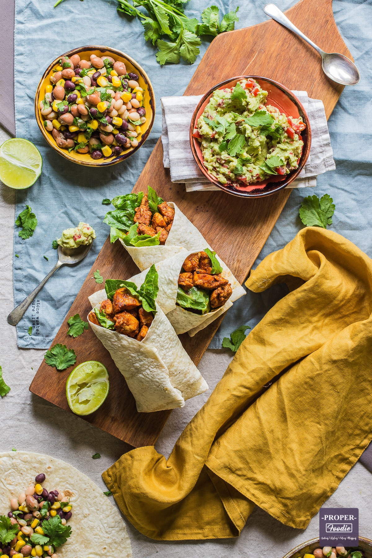 three chicken wraps on a board viewed from above with half a lime squeezed at the side and small bowls of bean salad and smashed avocado above