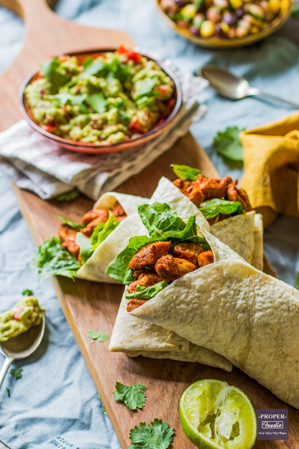 three chicken wraps presented on a long slim board with a bowl of guacamole and a squeezed lime