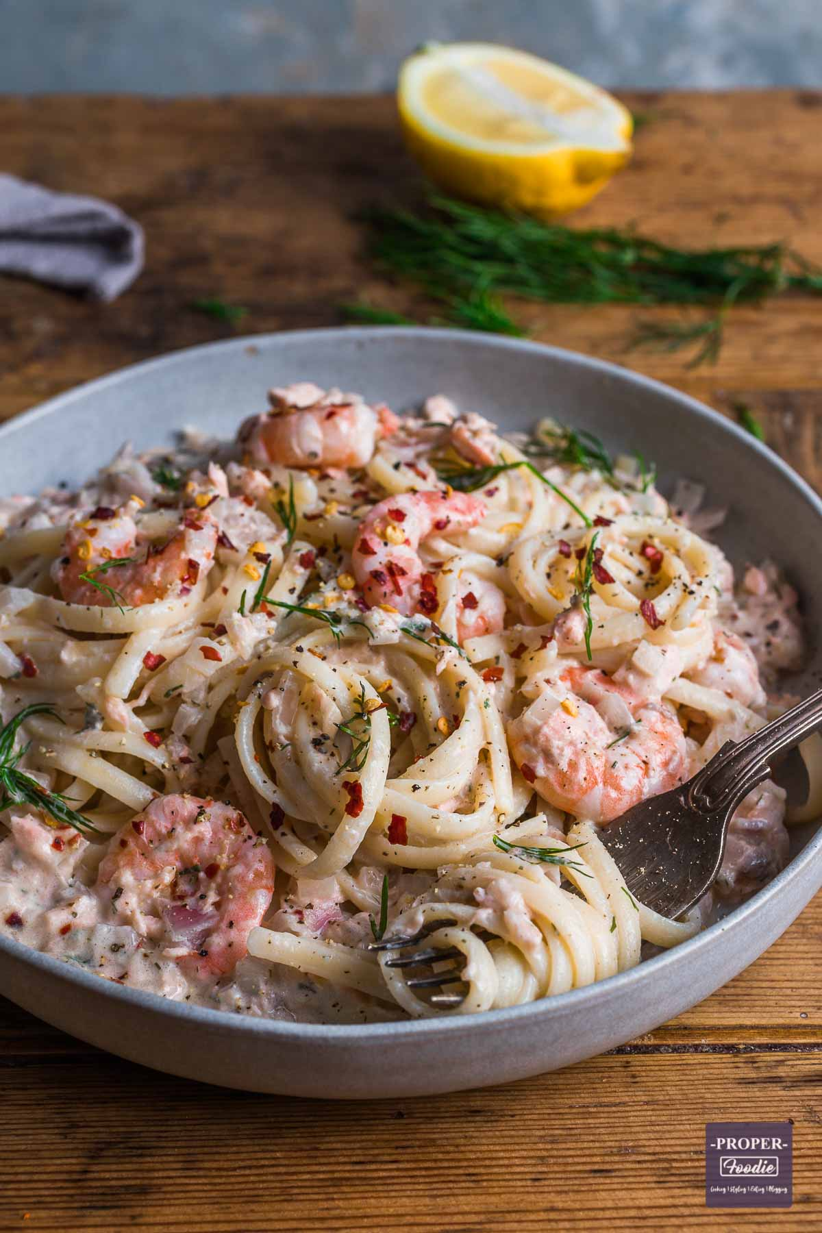 A bowl of linguine in a creamy sauce with salmon and prawns