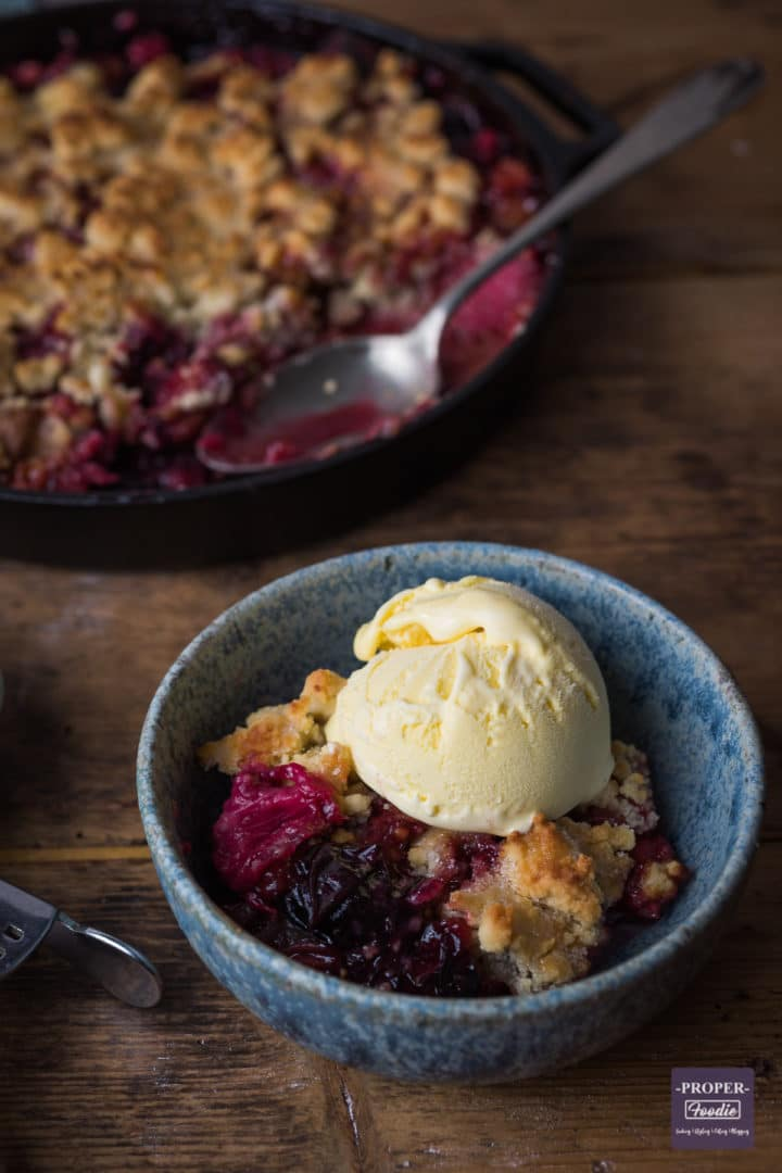 Plum and rhubarb crumble served up in a bowl with ice cream and pan with crumble in the background