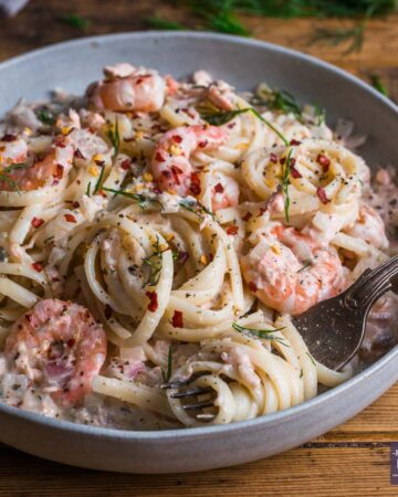 A bowl of linguine in a creamy sauce with salmon and prawns.