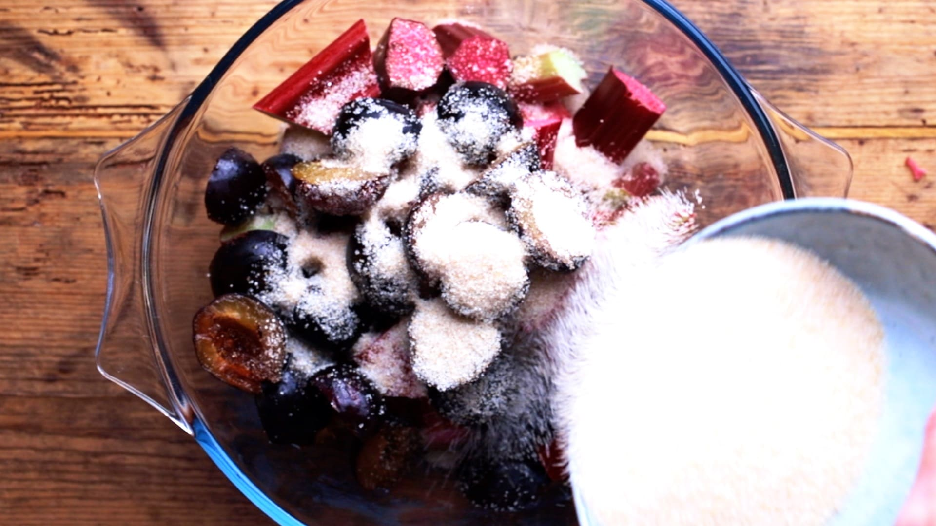 sugar being added to rhubarb and plums