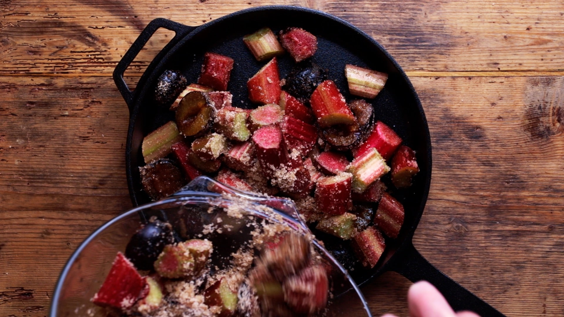 sugared rhubarb and plums being transfered to baking pan