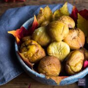Bowl of roasted and peeled chestnuts with autumnal leaves lining the bowl.