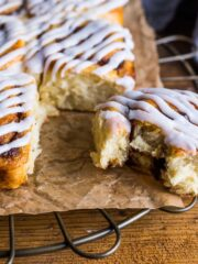 Baked cinnamon swirls stuck together in two side by side rows with icing on the top and one roll broken off with a bite taken.