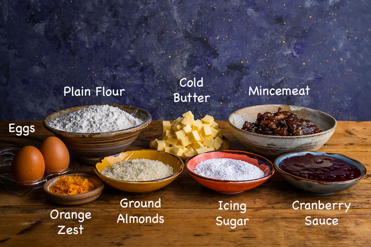 A display of all the ingredients needed to make mince pies with text overlay labelling each ingredient.