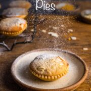 Single mince pie on a plate with a frangipane topping and sprinkles of icing sugar falling down on top. Overlay text: Frangipane Mince Pies.