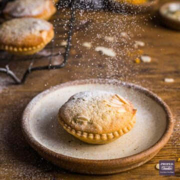 Single mince pie on a plate with a frangipane topping and sprinkles of icing sugar falling down on top.