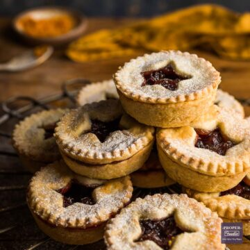 A stack of homemade mince pies with star shapes cut out of the pastry lids.