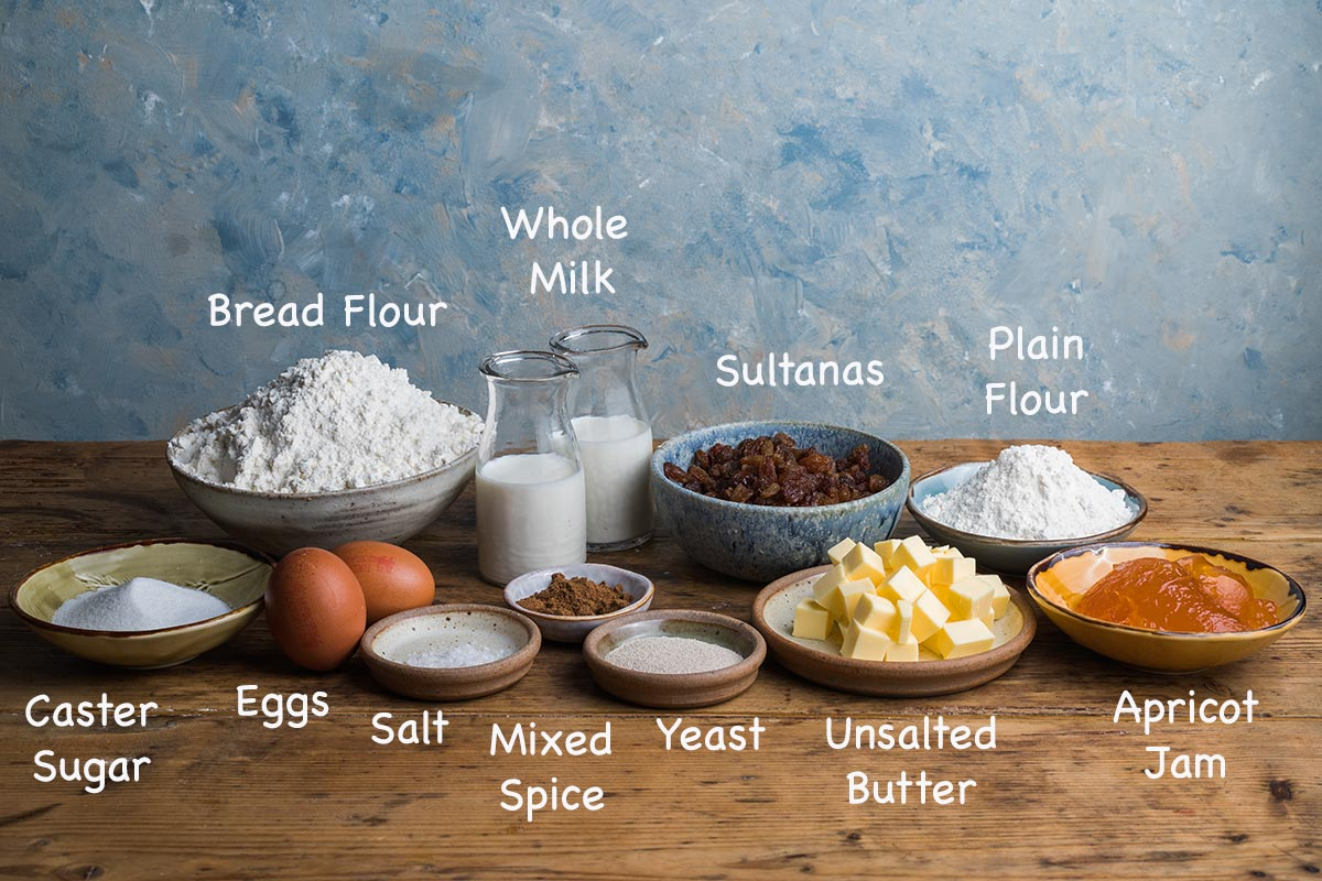 A display of the ingredients needed to make hot cross buns with text overlay stating each ingredients.