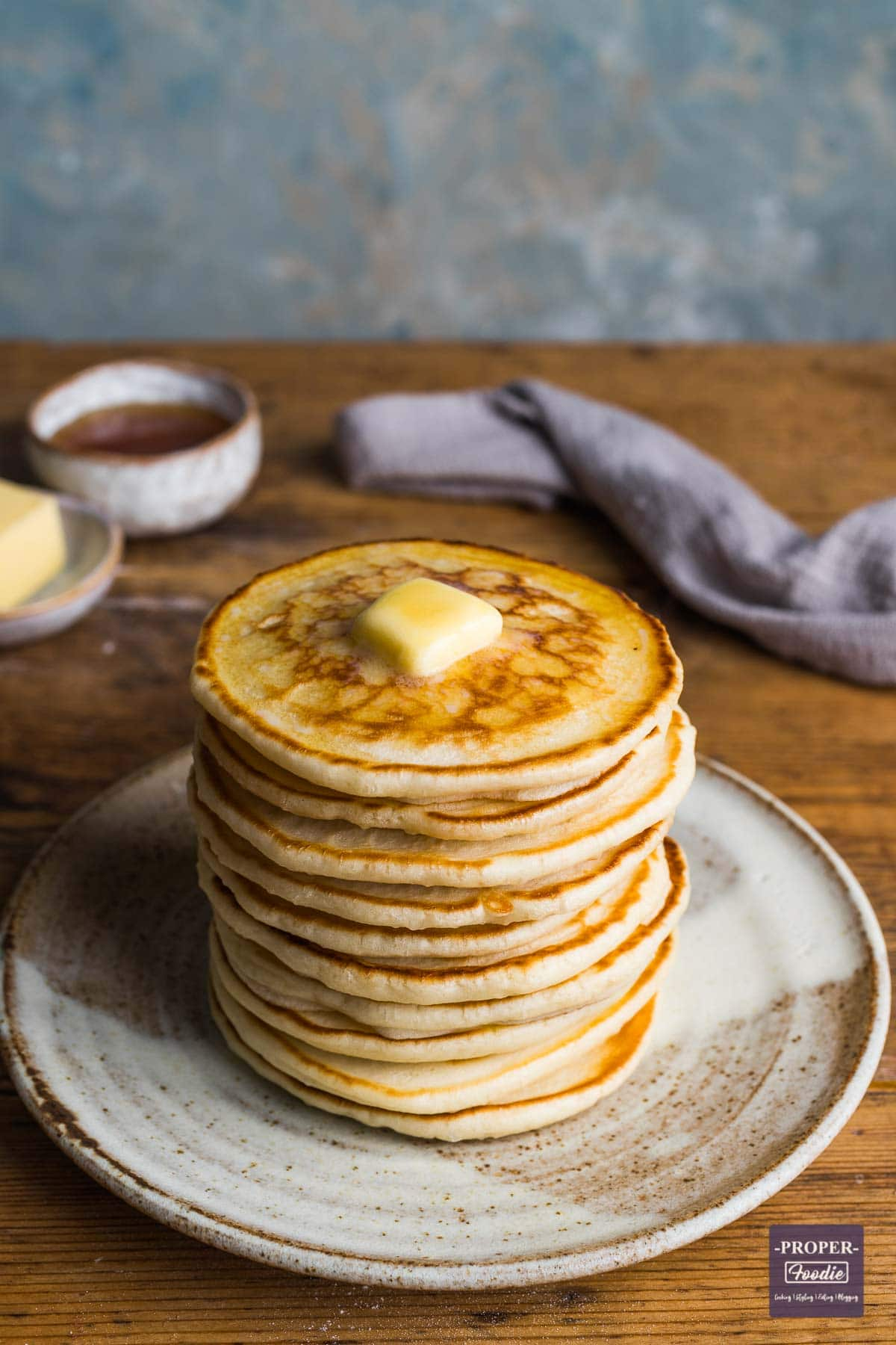 A tall stack of scotch pancakes on a plate with melted butter on top ad a small dish on honey in the background.
