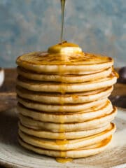 A tall stack of scotch pancakes on a plate with melted butter on top and honey being drizzled over with a wooden honey dipper.