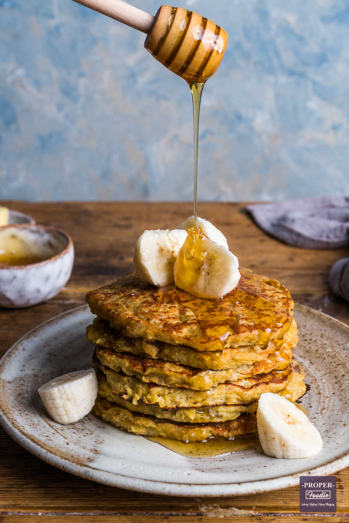 A stack of banana pancakes on a plate topped with slices of banana and a line of honey being poured over from honey dipper.