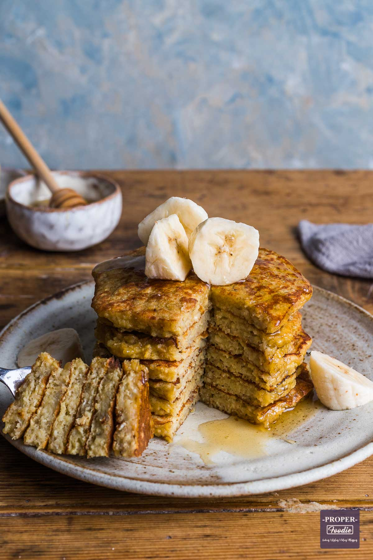 Stack of banana pancakes topped with sliced bananas, and with a wedge skewered and cut out from one side of the pancake stack and put to the side.