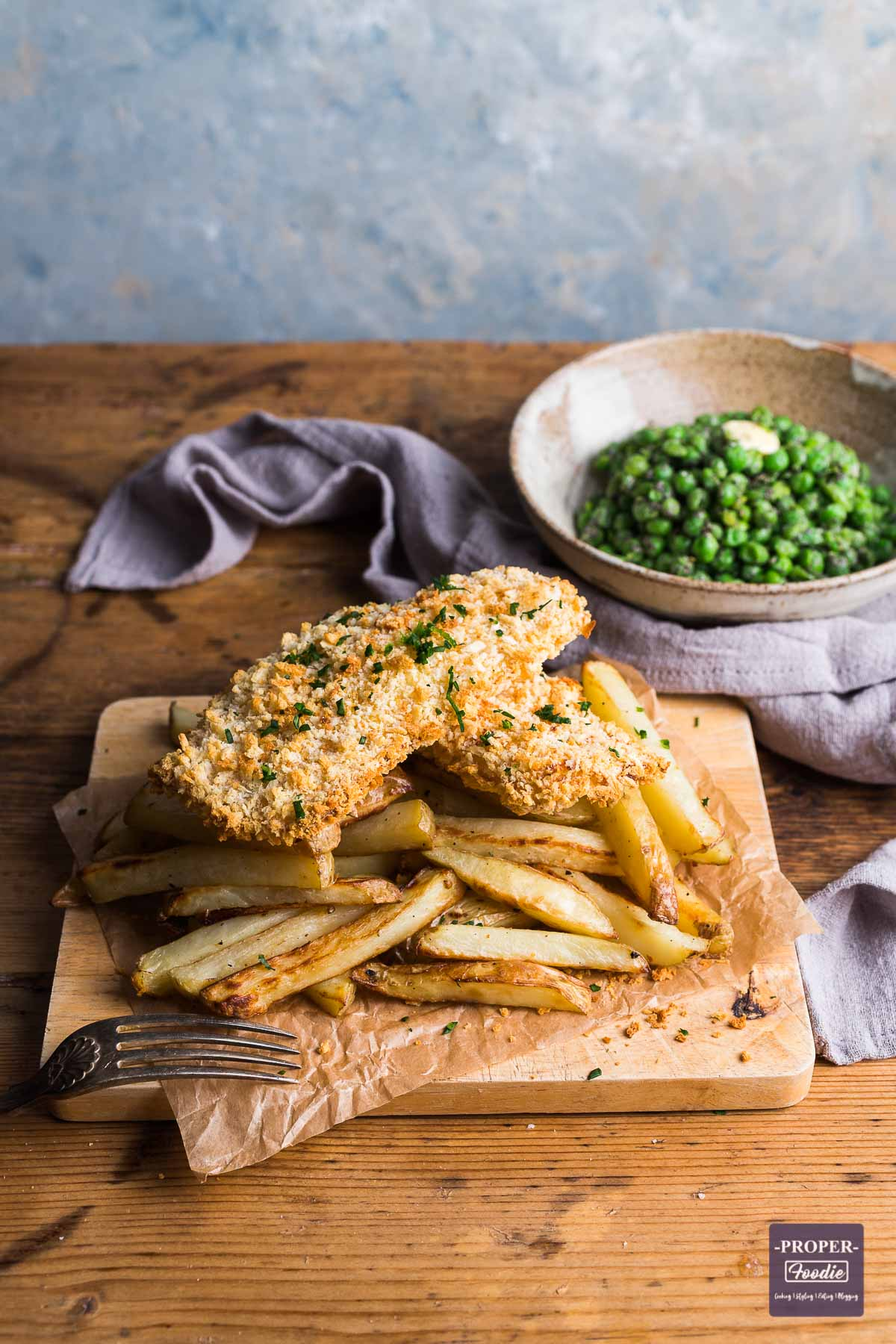 Bread crumbed fish fillets sat on a pile of homemade chips with a bowl of peas in the background topped with melting butter