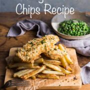 Homemade fish and chips on a wooden board with a bowl of garden peas in the background