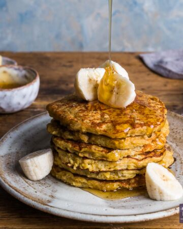 A stack of banana pancakes on a plate topped with slices of banana and a line of honey being poured over from above.