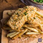 Two fillets of fish in golden bread crumbs sat on a pile of homemade oven chips