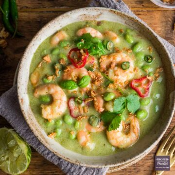 Thai green prawn curry served in a bowl and topped with fresh basil and chillies.